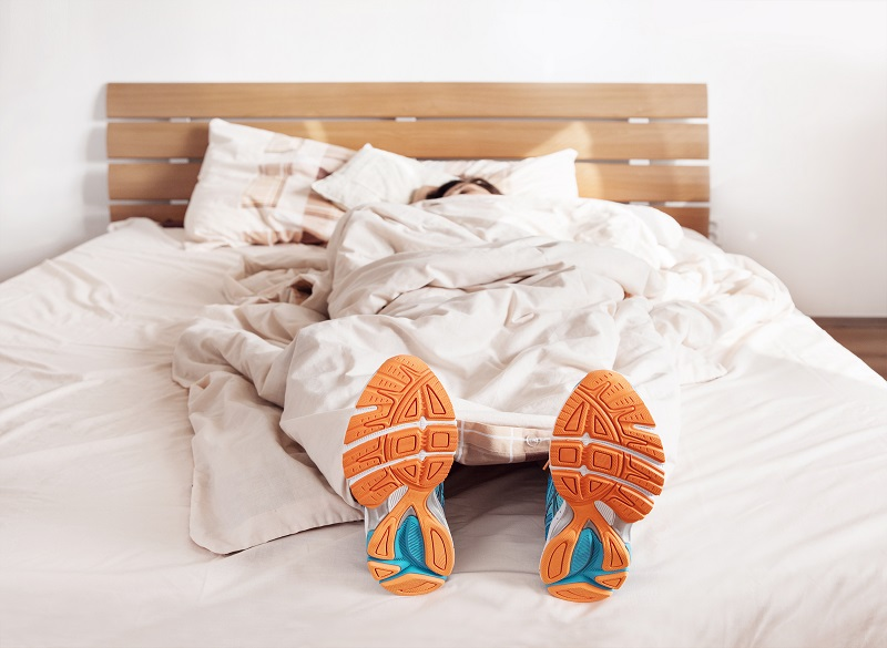 Person napping on bed in workout clothes to get better sleep.