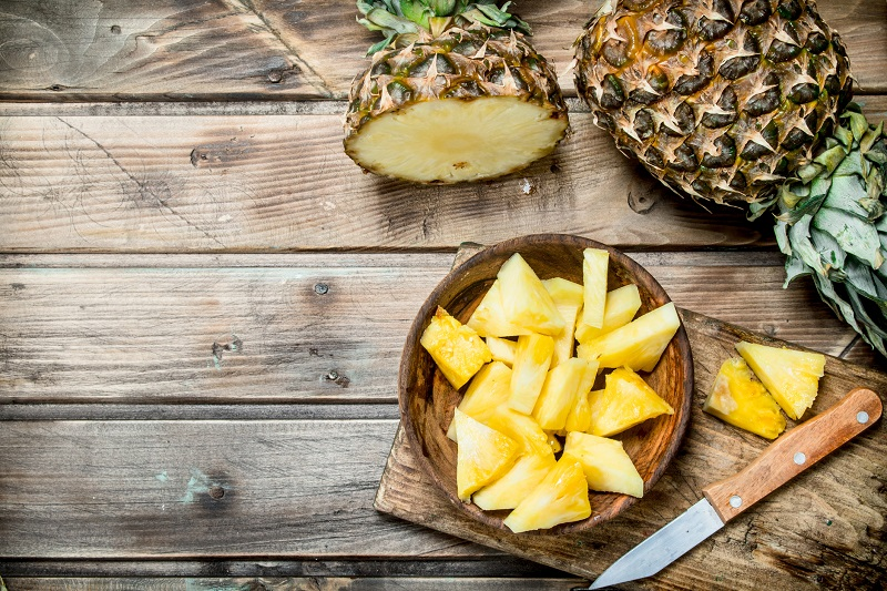 Whole pineapple and pineapple slices on a table. pear shaped body fat loss tips