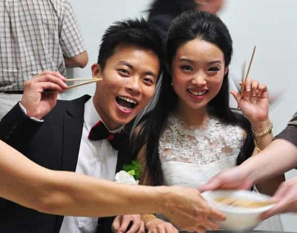 cute asian couple at their wedding holding chopsticks