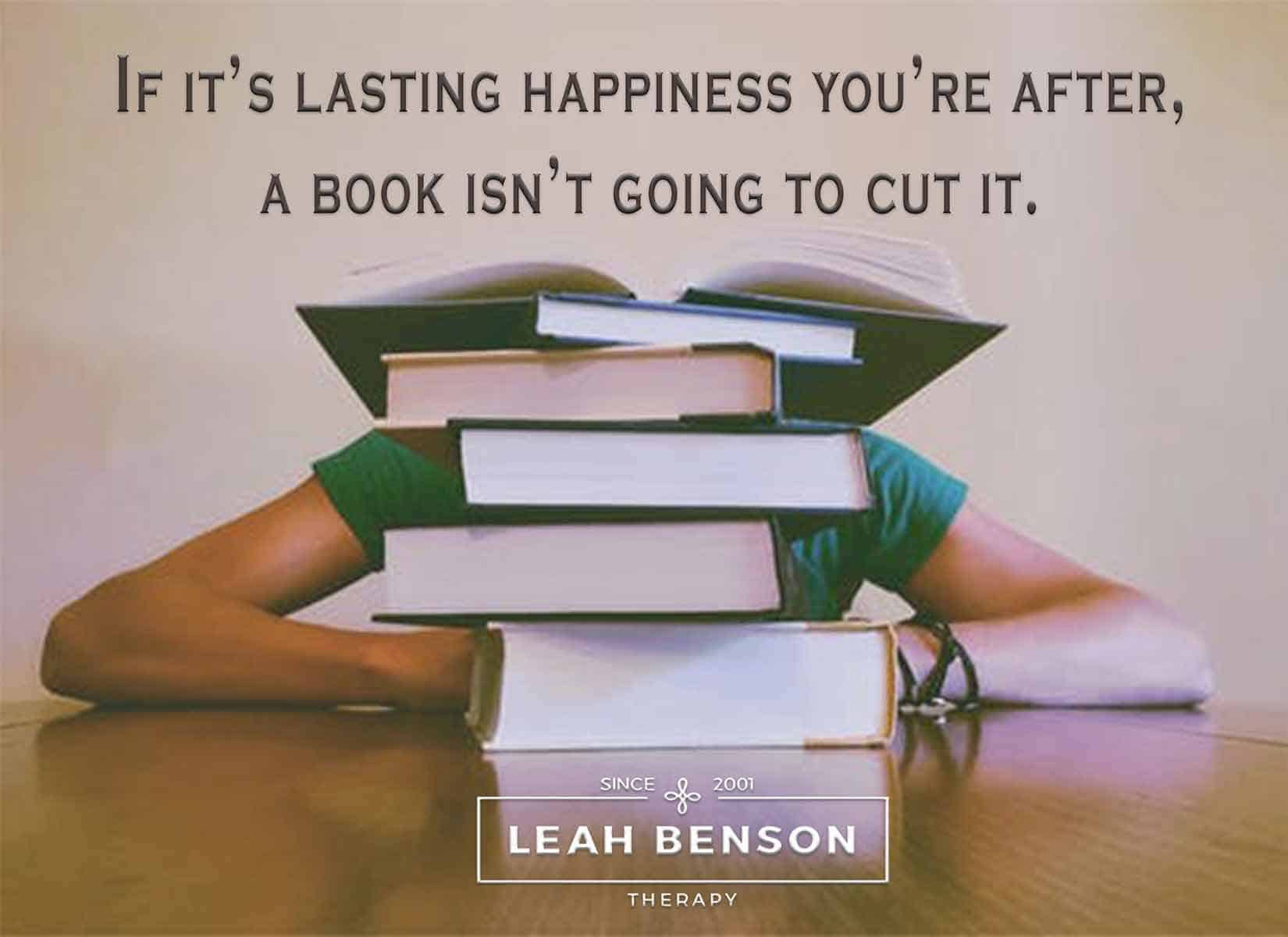 """Photo of person sitting behind a stack of books with the quote, """"If it's Lasting Happiness You're After, a Book isn't going to Cut It"""""""