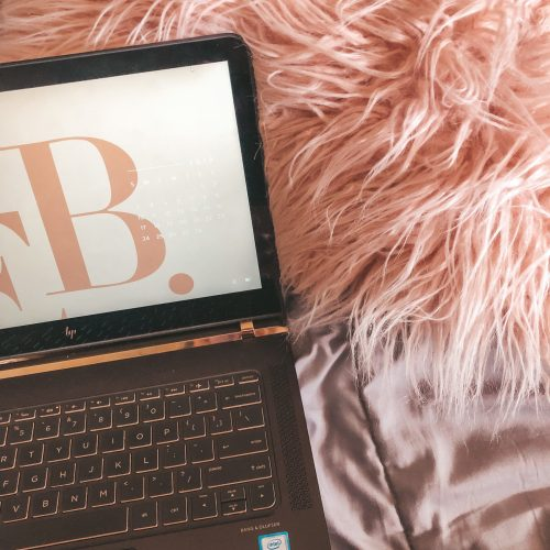 Fuzzy pink pillow with laptop in front of it that has a blush pink background