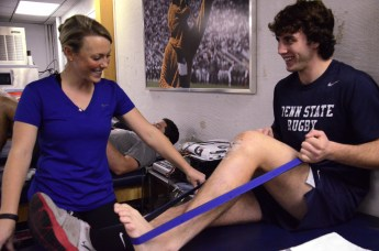Sarah Leslie, Penn State Rugby Athletic Trainer, works with captain Blaze Feury every day to strengthen his knee after tearing his ACL during a rugby match. On Nov. 8, 2013 in the East Area Locker Training Room, Leslie has Feury using resistance bands, the stationary bike and other small exercises.