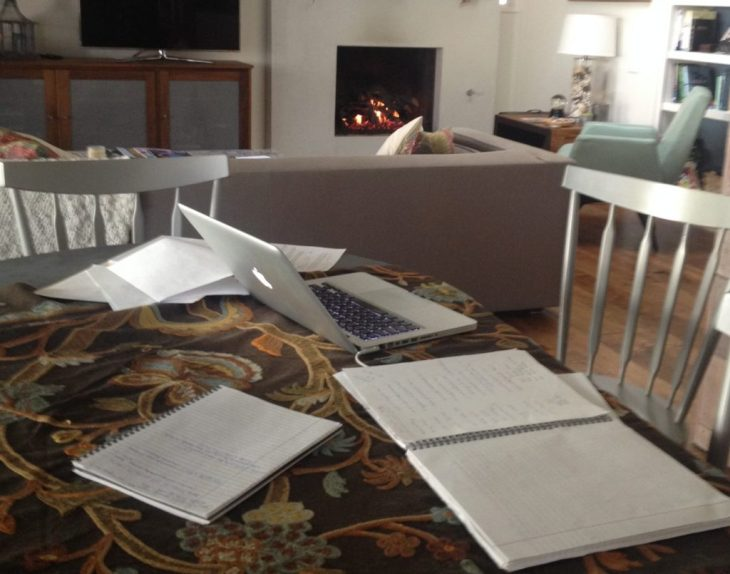 Laptop and notes at table in front of lit fireplace.