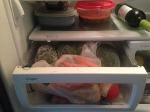 Inside a refrigerator with veggie bin open