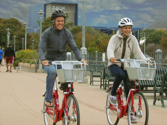 Couple riding B-cycles in Austin on Pfluger Pedestrian Bridge