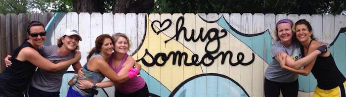 "Women runners hug in front of graffiti that says ""Hug Someone."""