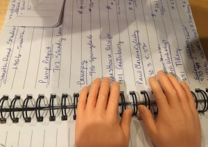 Photo of pair of tiny plastic hands and notebook.