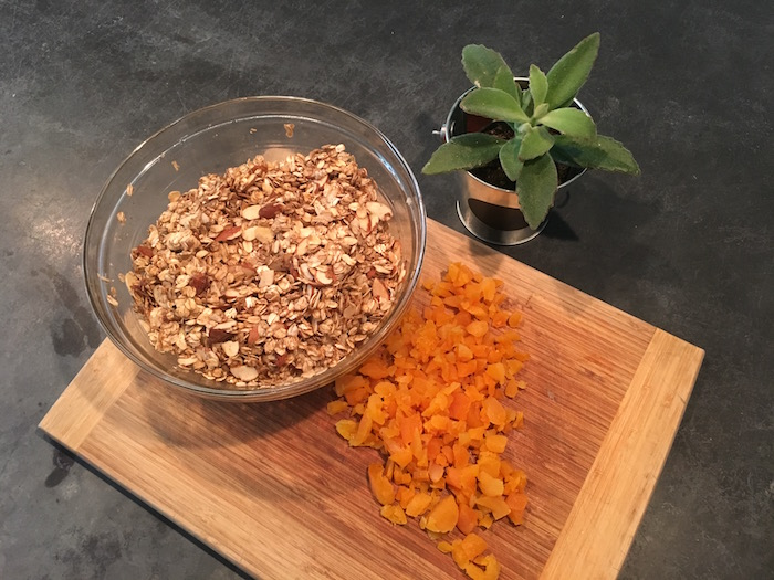 Bowl of ingredients and chopped apricots to make homemade granola.
