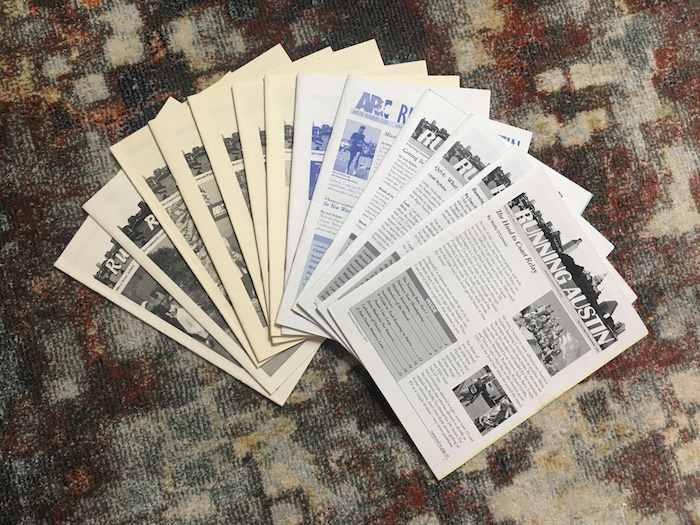 Print newsletters from the Austin Runners Club spread out in a fan.