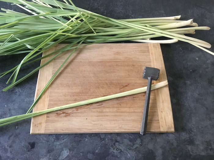 Using a meat mallet to tenderize lemongrass stalks
