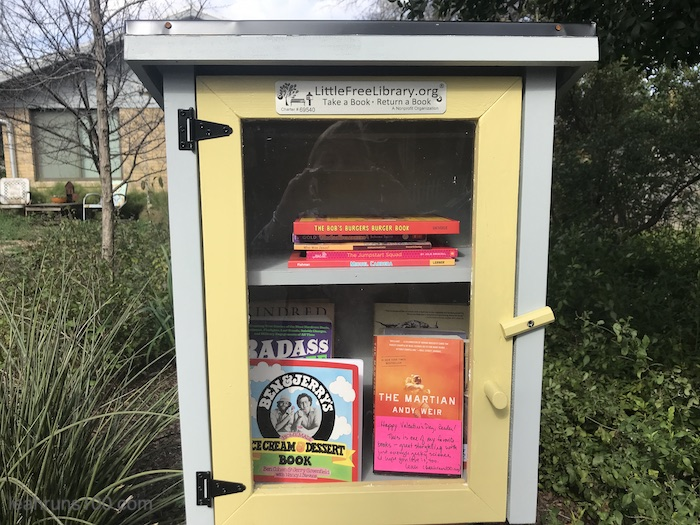 Blue and yellow Little Free Library with books including The Martian by Andy Weir