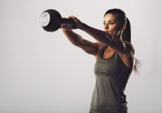 Image of young attractive female doing kettle bell exercise on grey background. Fitness woman working out. Crossfit exercise.