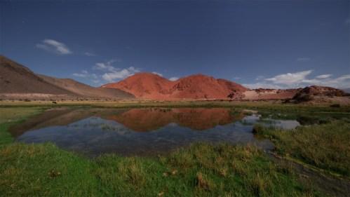 Laguna y montañas rojas
