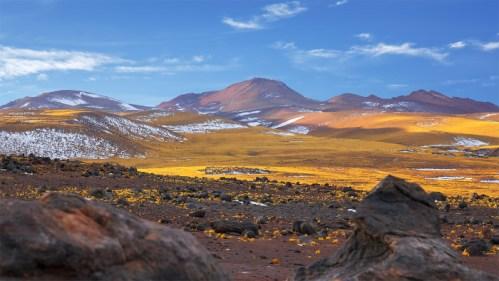 Montañas nevadas, piedra volcánica y atardecer