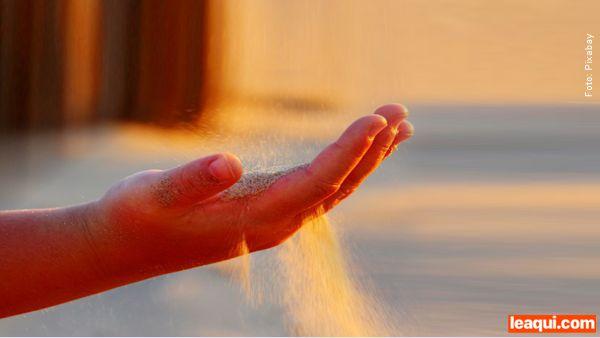 Mão deixando areia escapar por entre os dedos como sinal de desapego e perdão
