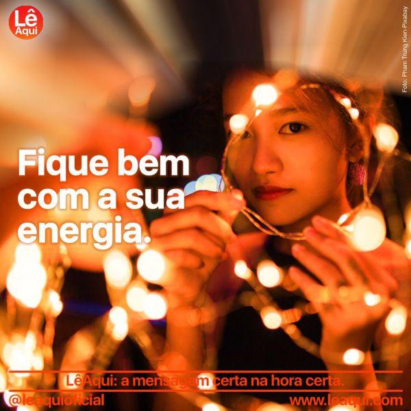 Moça por trás de cordões iluminados mostrando que está bem com sua energia.