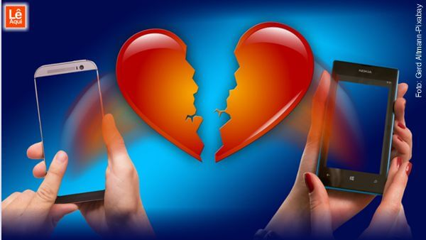 Mãos de homem e de mulher, cada uma num canto segurando um celular e no meio um coração partido