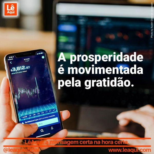 Pessoa segurando celular que mostra gráfico de economia, pois a prosperidade é movimentada pela gratidão.