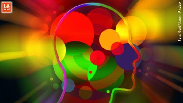Silhueta gráfica de uma cabeça com bolas coloridas representando as escolhas e a energia de atração.