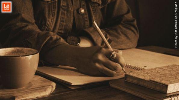 Mulher escrevendo em um caderno fazendo o diário interior,uma dica para que você crie felicidade