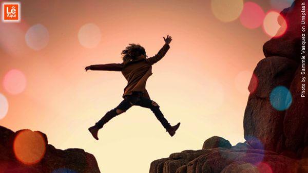 Mulher saltando sobre um abismo demonstrando que a fé é a força maior