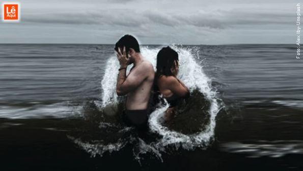 Homem e mulher no mar de costas um para o outro com as mãos cobrindo o rosto para não se decepcionar