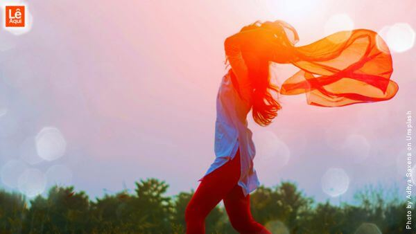 Mulher caminhando ao vento no campo para se libertar de suas limitações.