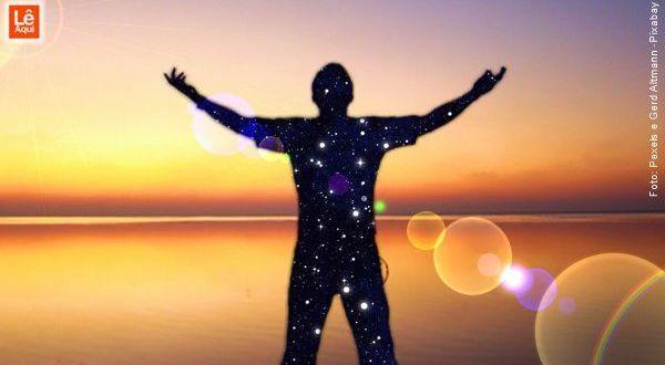 Silhueta de um homem com os braços abertos numa praia ao nascer do sol com a silhueta cheia de estrelas demonstrando o brilho das frases de Abraham-Hicks