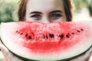 Moça com expressão alegre segurando uma fatia de melancia como se fosse um sorriso fazendo a valorização da autoestima