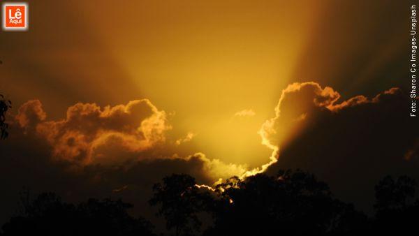 Nascer do sol com a dourada luz vencendo as densas nuvens afirmando o poder da fé.