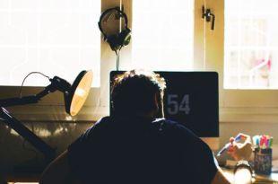 Homem trabalhando em um computador na sua casa mostrando o trabalho remoto