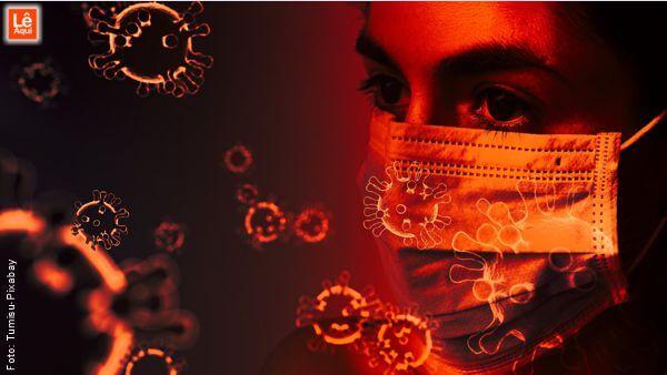 """Rosto de mulher usando máscara cirúrgica com ilustrações do vírus """"flutuando"""" demonstrando a necessidade de que Vibremos amor e luz para o mundo"""