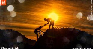 Homem ajudando outro a subir uma montanha demonstrando como curar emoções feridas