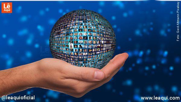 mão segurando um globo com inúmeras fotos de pessoas mensagem Dalai Lama Dia Terra