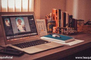 mesa em um canto com janela ao fundo onde existe um computador, um telefone celular, blocos de anotação e alguns livros mostrando a tendencia do mercado de trabalho pós-pandemia