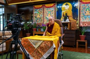 Foto de Dalai Lama sentado a uma mesa em sua casa com câmera onde são transmitidos Dalai Lama ensinamentos