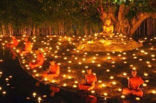 foto do ritual comemorativo do vesak com a estatua de buda sob uma figueira e vários monges em posição de lótus às margens de um rio com inúmeras luminárias dispostas ao derredor para ilustrar pandemia mensagem Dalai Lama