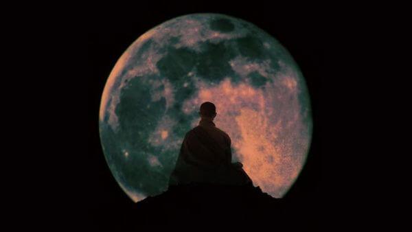 montagem fotográfica de um budista em posição de meditação com uma imensa lua cheia de fundo simbolizando a Lenda de Wesak