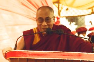 Imagem do Dalai Lama falando ao microfone em palestra mantra purifica