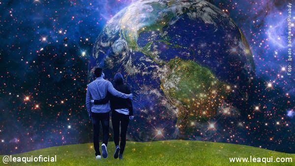 casal abraçado caminhando em um campo com o planeta terra no céu posição espiritual da Terra