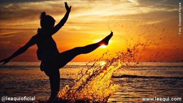 mulher em uma praia à beira do mar chutando a água em um por do sol vivo de verdade