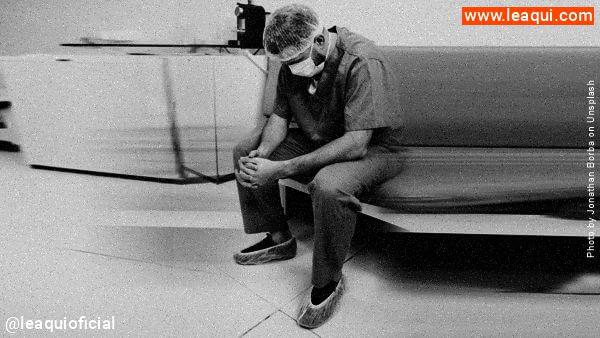 Médico com roupa de trabalho usando máscara sentado com a cabeça baixa vivendo os dramas médicos covid-19