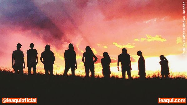 Muitas pessoas confraternizando-se ao por do sol no alto de uma colina emocional novo coronavírus