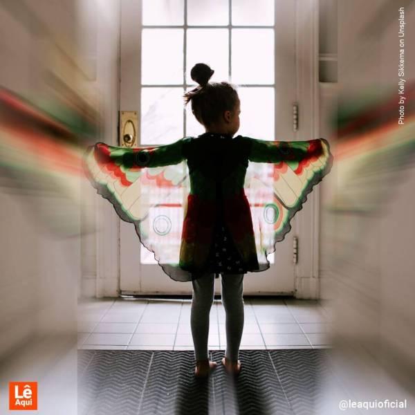 menina pequena com fantasia de de borboleta olhando pela janela crianças pandemia