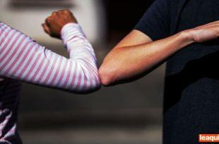 uma mulher e um homem cumprimentando-se usando o toque dos cotovelos como orientação do guia pandemia