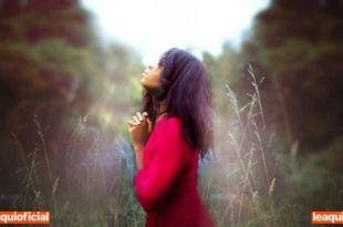 mulher em meio a um bosque com as mãos postas em oração por quem rezar