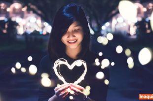 uma moça segurando um arranjo luminoso em forma de coração simbolizando encontrar consigo mesmo