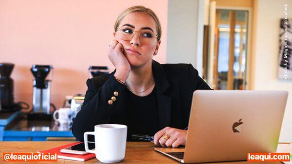 uma mulher em um escritório com um computador à sua frente mas a mulher está olhando para o alto não fazendo nada procrastinação