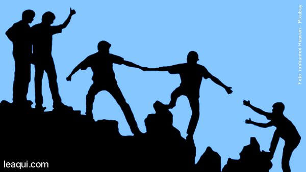 ilustração em forma de silhueta com diversas pessoas ajudando-se para subir num morro bondade contagiosa