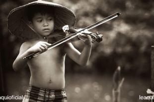 menino vietnamita sem camisa e chapéu típico da região tocando violino em uma floresta explicação para o talento